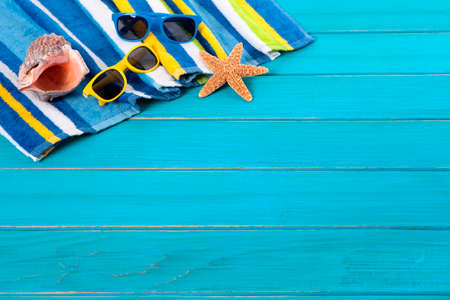 painted wood: Beach scene with striped towel, sunglasses, starfish and seashell on old weathered blue painted wood decking.  Space for copy.