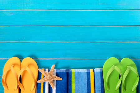 flops: Beach border scene with striped towel, flip flops and starfish on old weathered blue painted wood decking.  Space for copy.