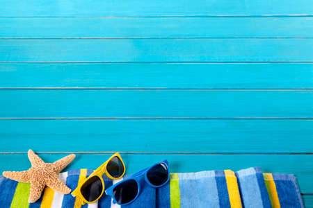 decking: Beach border scene with striped towel, sunglasses and starfish on old weathered blue painted wood decking.  Space for copy.