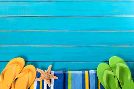 Beach scene with striped towel, flip flops and starfish on old weathered blue painted wood decking.  Space for copy. Banco de Imagens