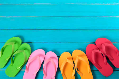 flops: Row of colorful flip flops on old weathered blue painted beach decking.  Space for copy.