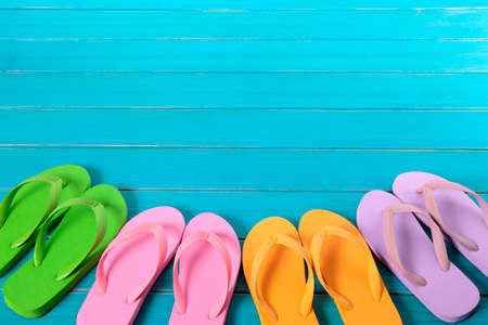 Row of colorful flip flops on old weathered blue painted beach decking.  Space for copy.
