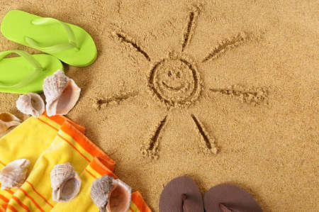 Caribbean beach background with smiling sun drawing, towel and flip flops 스톡 콘텐츠