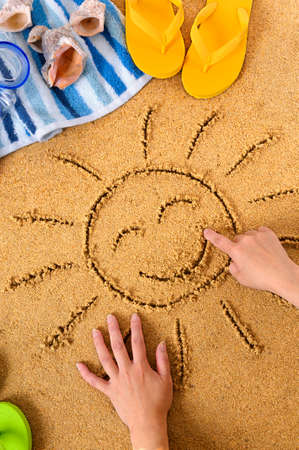Child drawing a smiley sun in sand with towel, seashells and flip flops
