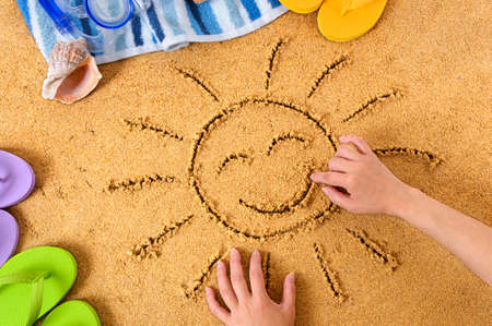 Child drawing a smiley sun in sand with towel, seashells and flip flops photo