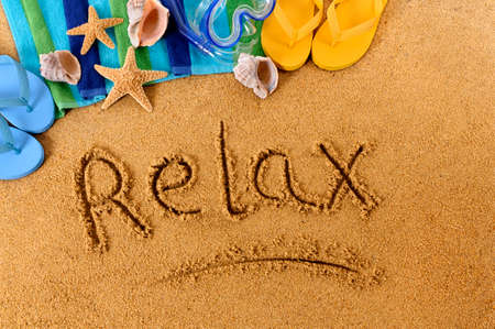 beach towel: The word Relax written on a sandy beach, with scuba mask, beach towel, starfish and flip flops Stock Photo