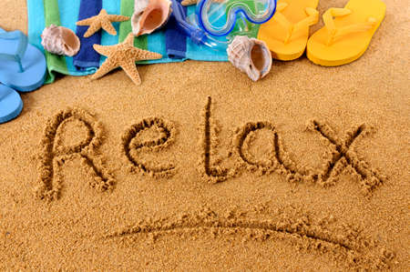 flops: The word Relax written on a sandy beach, with scuba mask, beach towel, starfish and flip flops Stock Photo