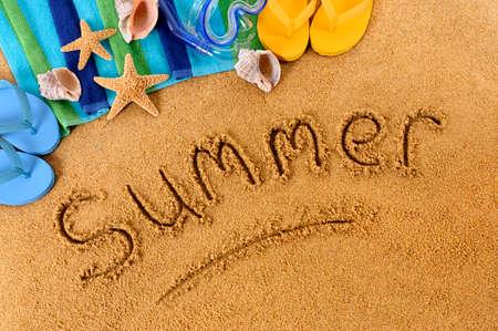 The word Summer written on a sandy beach, with scuba mask, beach towel, starfish and flip flops