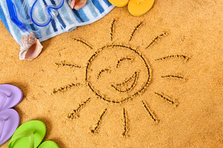 Smiley face sun drawn in sand, with towel, scuba mask, seashells and flip flops