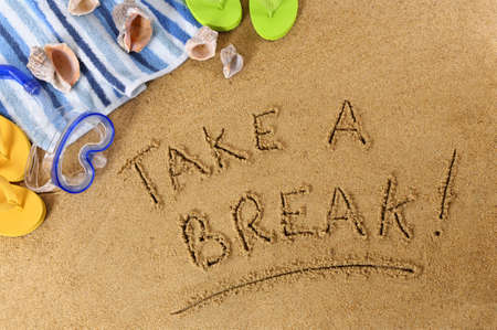 take a break: Beach background with towel, scuba mask and flip flops and the phrase Take A Break written in sand Stock Photo