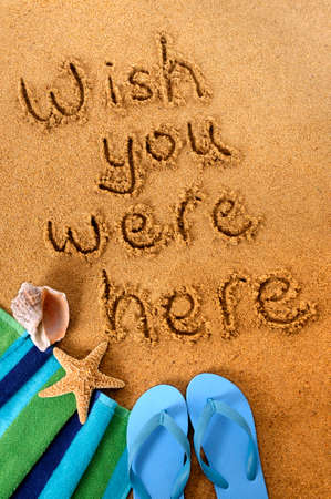 beach towel: Classic postcard message written on a sandy beach, with beach towel, starfish and flip flops