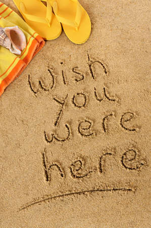 beach towel: Classic postcard message written in sand with beach towel, seashells, and flip flops Stock Photo