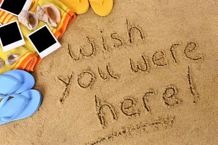 beach towel: Classic postcard message written in sand with beach towel, seashells, flip flops and blank photo prints
