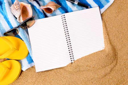 Achtergrond van het strand met handdoek, slippers en blanco notebook.