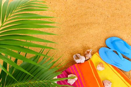 Beach achtergrond met palmbladeren, handdoek en slippers. Ruimte voor exemplaar. Stockfoto