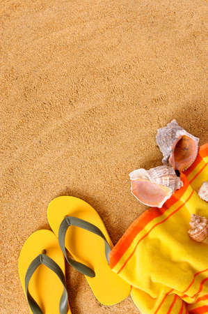 Beach background with yellow towel and flip flops.  Space for copy.