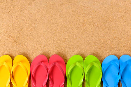 space for copy: Flip flops in a row on a sandy beach.  Space for copy.