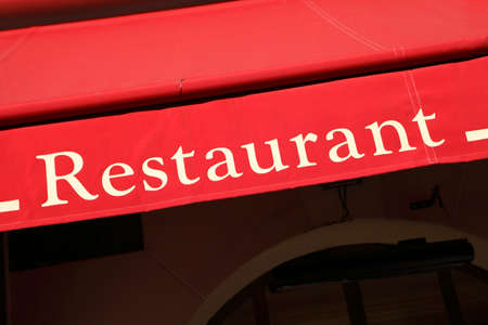 french text: Bright red restaurant entrance canopy in Paris.