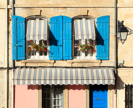 Typical French provencal style windows with blue shutters and flower boxes.