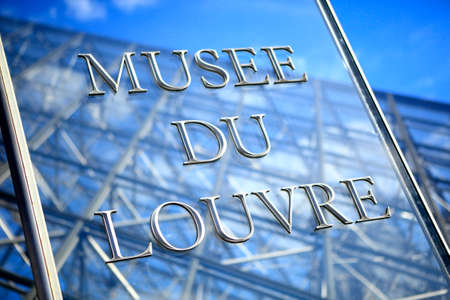 entrance sign: Glass and stainless steel entrance sign at the Louvre Museum in Paris with part of the famous glass pyramid in the background.  Note: lots of bright specular highlights. Editorial