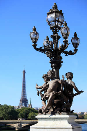 street lamp: Ornate renaissance street lamp on the famous Pont Alexandre III bridge in central Paris with River Seine and Eiffel Tower in the distance.
