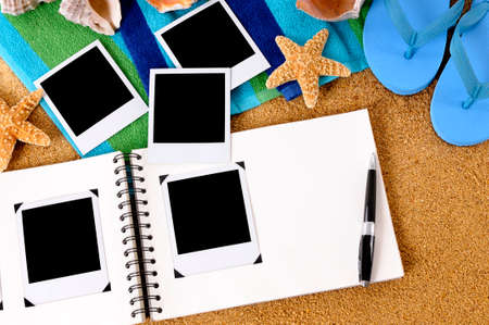 Foto album op een zandstrand, met lege fotoprints, strandlaken, zeesterren en flip flops