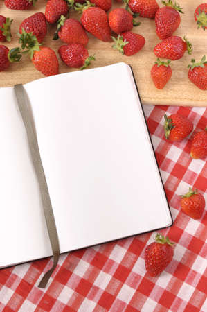 Strawberries with blank recipe book on a chopping board and red check tablecloth. Foto de archivo