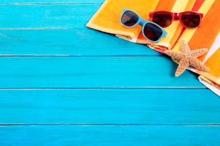 Scène van het strand met oranje gestreepte handdoek, zeester en zonnebril op oude blauw geschilderde houten terras. Scherpe focus op de zonnebril. Ruimte voor exemplaar.