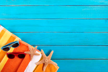 Beach scene with orange striped towel, starfish and sunglasses on old blue painted wood decking.  Space for copy.