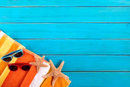 étoile de mer: Scène de plage avec une serviette à rayures orange, étoiles de mer et des lunettes de soleil sur la vieille peint en bleu platelage en bois. Espace pour la copie.