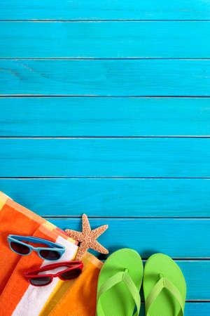 Beach scene with orange striped towel, pairs of sunglasses and flip flops on old blue painted wood decking.  Space for copy. Standard-Bild