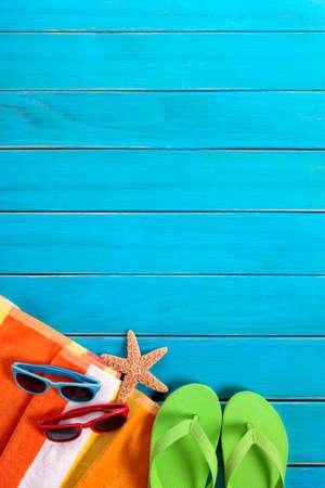 Scène van het strand met oranje gestreepte handdoek, paren van zonnebrillen en flip flops op oude blauwe geschilderde houten terras. Ruimte voor exemplaar. Stockfoto