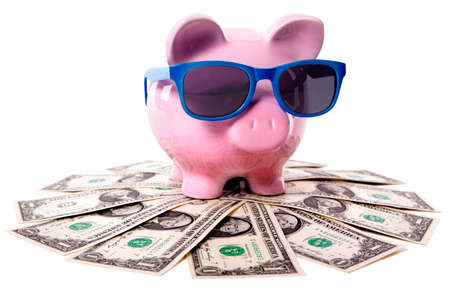 Pink piggy bank wearing blue sunglasses and standing on a pile of US dollars.  Isolated. Banco de Imagens
