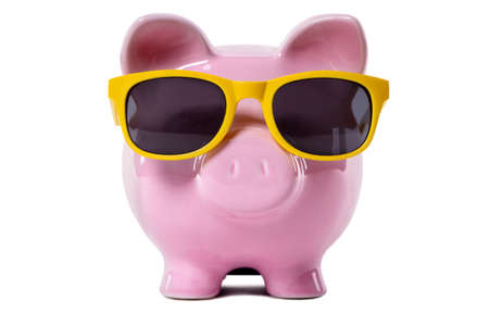 Pink piggy bank wearing yellow sunglasses.  Isolated on white. Standard-Bild
