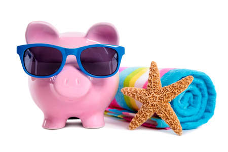 Pink piggy bank wearing blue sunglasses on a beach with starfish and beach towel.  Isolated on white. photo