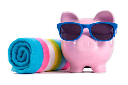 Pink piggy bank with blue sunglasses and candy stripe beach towel. photo