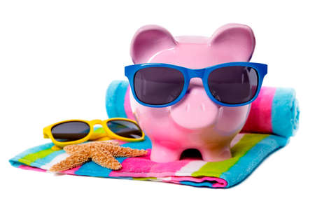 retirement fund: Pink piggy bank with blue sunglasses on a candy stripe beach towel.  Isolated on white.