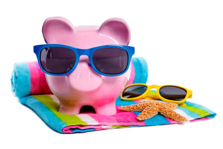 Pink piggy bank with blue sunglasses on a candy stripe beach towel.  Isolated on white. photo
