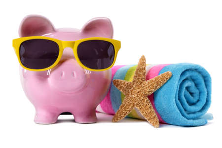 Pink piggy bank wearing yellow sunglasses on a beach with starfish and beach towel.  Isolated on white. Stock Photo