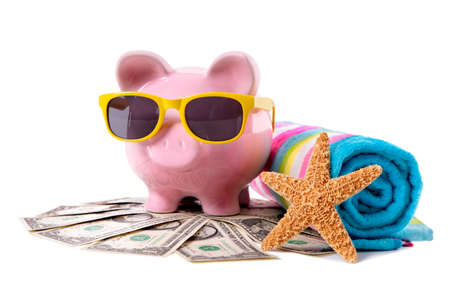 Pink piggy bank with yellow sunglasses and travel money photo