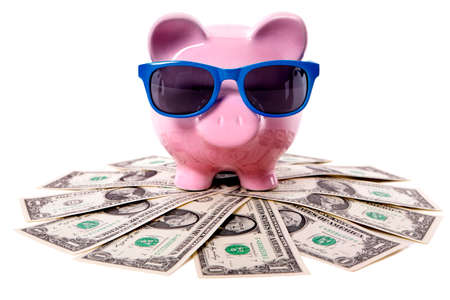 banks: Pink piggy bank wearing blue sunglasses and standing on a pile of US dollars. Stock Photo