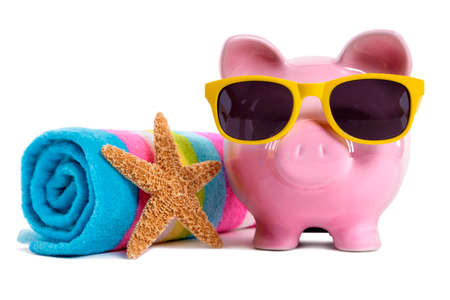 Pink piggy bank wearing yellow sunglasses on a beach with starfish and beach towel.  Isolated on white. Standard-Bild