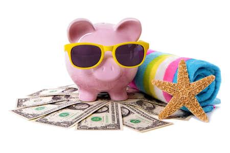Roze spaarvarken met gele zonnebril, zeesterren en snoep streep strandlaken staande op een stapel van Amerikaanse dollars. Stockfoto
