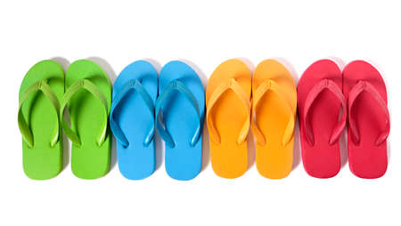 Row of colorful flip flops isolated against a white background.