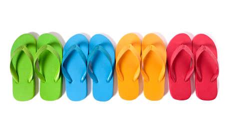 Rij van kleurrijke flip flops geïsoleerd tegen een witte achtergrond.