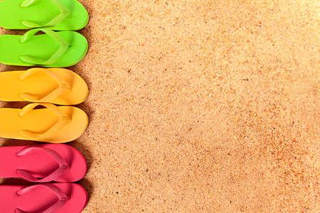 flipflops: Flip flops in a row, beach sand background