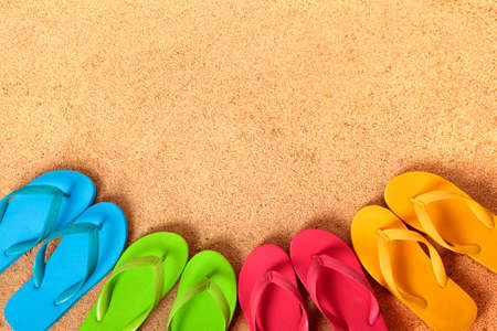 flip flops: Row of flip flops on a sandy beach background.  Copy space.