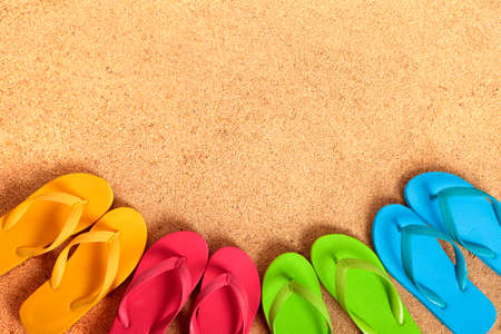 flops: Row of flip flops on a sandy beach background.  Copy space.