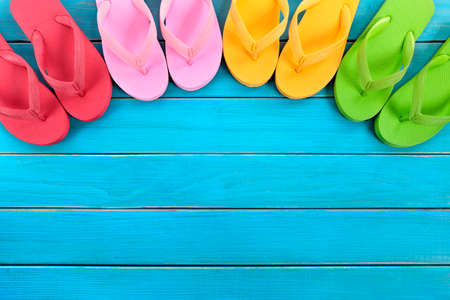 Semi circle of colorful flip flops on old weathered blue painted beach decking.  Space for copy.