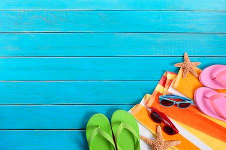 Scène van het strand met oranje gestreepte handdoek, zeester, zonnebril en slippers op de oude blauwe houten terras. Ruimte voor exemplaar. Stockfoto